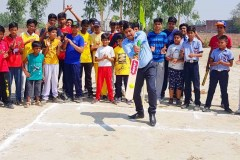 Sport officer enjoy cricket with children hit the ball